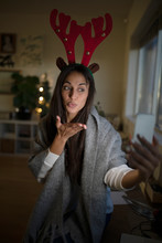 Young Woman In Christmas Antlers Taking Selfie And Blowing A Kiss