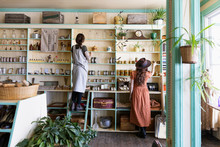 Female Business Owners Arranging Display In Apothecary Shop