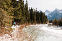 Friends Fat Biking On Snowy Trail Along Frozen River With Mountains In Background