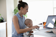 Mother With Baby Son Working From Home, Using Laptop In Kitchen