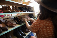 Woman Shopping For Shoes In Vintage Shop