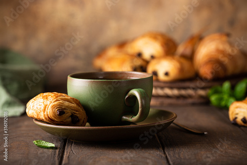 Green cup of tea with mini chocolate bun, puff pastry on old wooden table Canvas Print