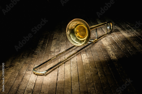 Photo golden brass instrument trombone lies on a dark brown wooden stage in the rays of light