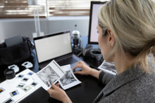 Female Photographer Reviewing Negatives In Office