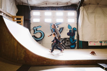 Father And Daughter Running Up Indoor Skate Park Ramp