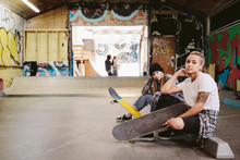 Portrait Confident, Cool Young Female Skateboarders At Indoor Skate Park