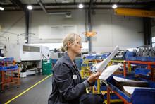 Female Machinist Examining Paperwork In Factory