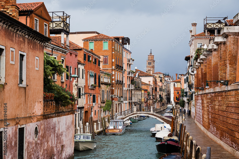Fototapeta bridge above canal, motor boats and ancient buildings in Venice, Italy