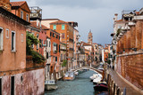 bridge above canal, motor boats and ancient buildings in Venice, Italy