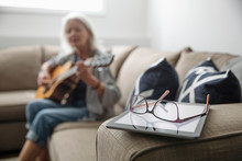 Eyeglasses On Digital Tablet With Senior Woman Playing Guitar In Background