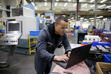 Male Machinist Using Laptop In...