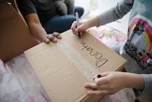 Girl Writing On Donation Box