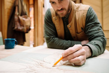 Male Artist Sketching At Table
