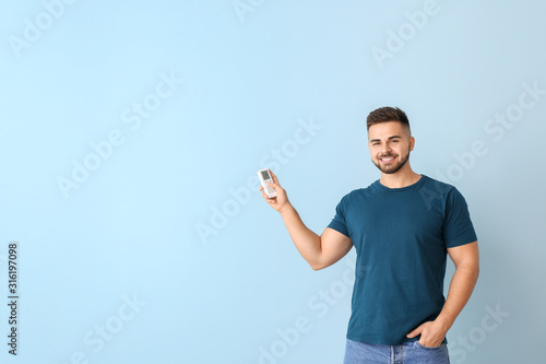 Young man with air conditioner remote control on color background Canvas Print