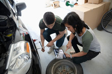 Mother And Son With Digital Tablet Learning To Change Car Tire In Garage