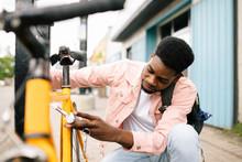Young Man Locking Bicycle On Sidewalk