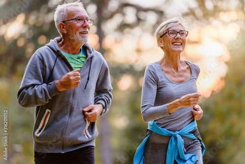 Leinwand Poster Cheerful active senior couple jogging in the park