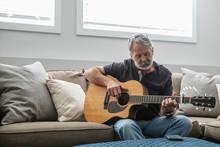Senior Man Playing Guitar On L...