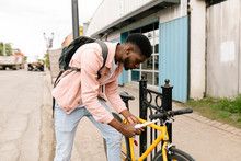 Young Man Locking Bicycle On S...