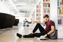Student Sitting On Floor Reading Book In Library