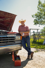 Mature Man Leaning On Pickup Truck With Hood Up