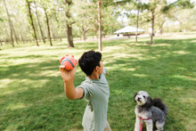 Boy Throwing Ball For Dog In Urban Park