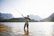 Woman Fly Fishing In Sunny, Scenic Lake
