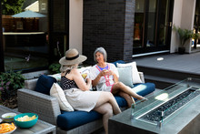 Senior Women Friends Drinking Margaritas On Summer Patio