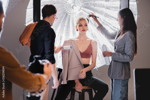 Fotografia selective focus of stylist using lint roller and hairstylist doing hairstyle to