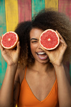 Portrait Playful Young Woman With Grapefruit Slices