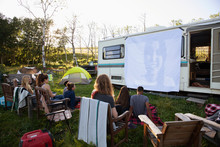 Group Of Friends Sitting Outside Motorhome Watching Movie