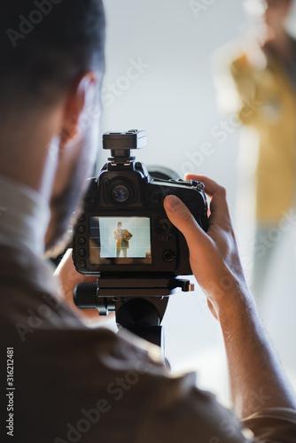 Obraz selective focus of photographer taking photo of model with digital camera on backstage - fototapety do salonu