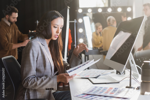 attractive producer sitting at table and looking at references on backstage Canvas Print