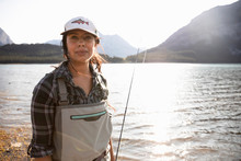 Portrait Confident Woman Fly Fishing At Sunny Lake