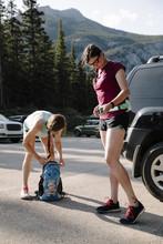 Female Hikers Preparing In Sunny Parking Lot