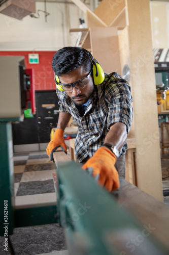 Young man wearing ear defenders sawing wood in maker space - 316214610