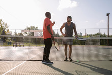 Two Men Talking Over Tennis Net