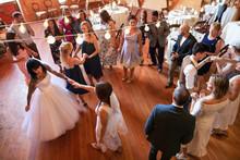 Wedding Guests And Lesbian Brides Dancing At Wedding Reception
