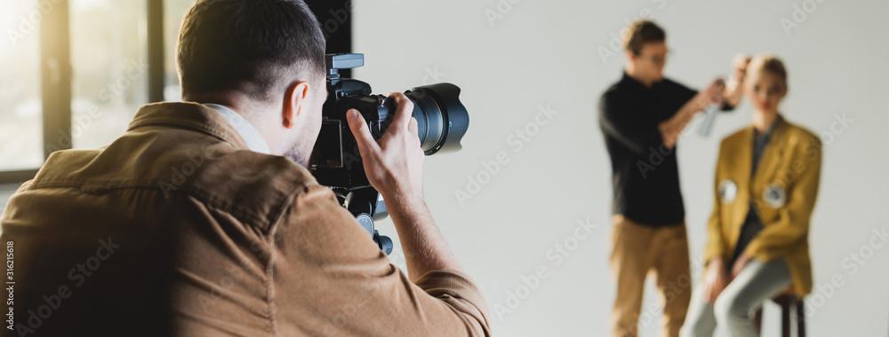 Fototapeta panoramic shot of photographer taking photo of model and hairstylist