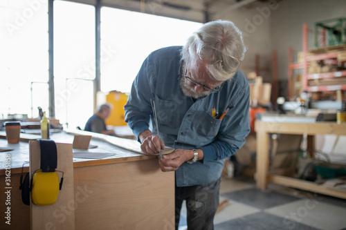 Carpenter measuring wood in workshop - 316215858