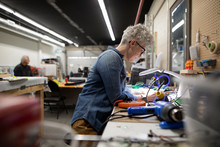Mature Woman Working With Electrical Equipment In Maker Space