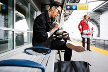 Young Man On Train Platform With Notebook And Pen
