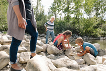 Two Children Playing On Riverbank With Grandmother