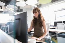 Businesswoman Using Desktop Computer In Modern Office