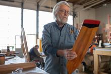 Senior Man In Carpentry Workshop Examining Handmade Wooden Oar