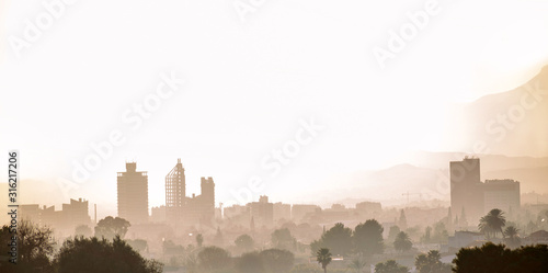 Cityscape of Murcia during a foggy sunset. Silhouette of building in Murcia city, Spain.