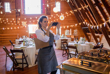 Female Caterer With Camera Phone Preparing Buffet Line At Wedding Reception