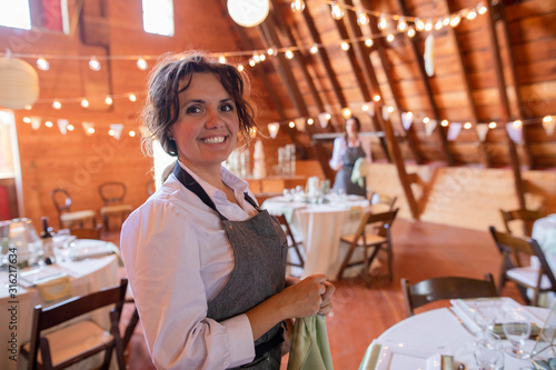 Portrait confident female server preparing for wedding reception - 316217634