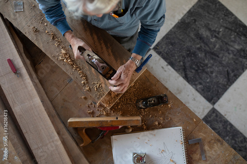 Overhead view of carpenter planing wood in workshop - 316218473