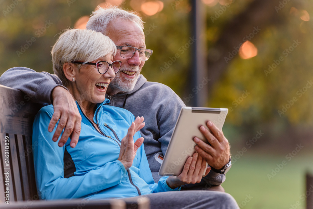 Fototapeta Smiling senior active couple sitting on the bench looking at tablet computer. Using modern technology by elderly.